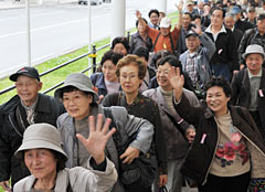 One hundred people currently living in temporary housing in Fukushima arrive in Okinawa