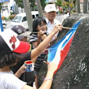 Miyara and local children clean and repaint 730 monument