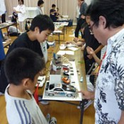 Pupils of Kaneshi Elementary School work under professionals to create models of their dream shop