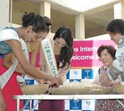 Miss International contestants race against locals removing bean sprouts roots