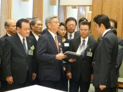 Okinawan leaders hand a petition to Prime Minister Abe requesting the easing of the base-hosting burden