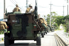U.S. military vehicles enter restricted road