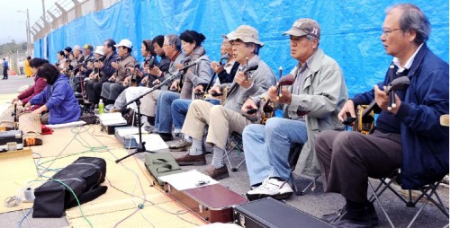 20 <em>sanshin</em> players perform, protesting against new US military base construction