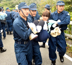 Riot police officers forcibly remove protestors on the morning of August 22 in Higashi Village, Takae.