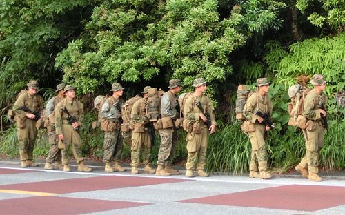 Rare scene in Japan: US servicemen carrying guns walk along road in Takae