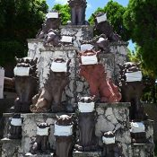 Fifteen Shisa statues at Ginowan City Hall wear masks in spite of the blazing sun