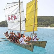 The Olympic torch races through the Kerama blue sea aboard a sabani boat paddled by Zamami middle schoolers